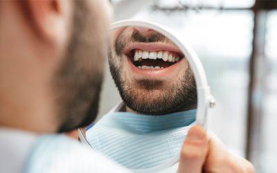 Hombre sonríe con empastes dentales en Carabanchel